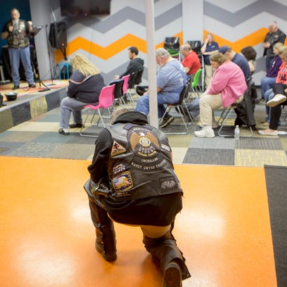 A member kneels to pray at a service of the Biker Church