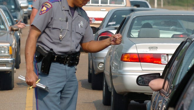 A Mississippi Highway patrolman reads a driver license