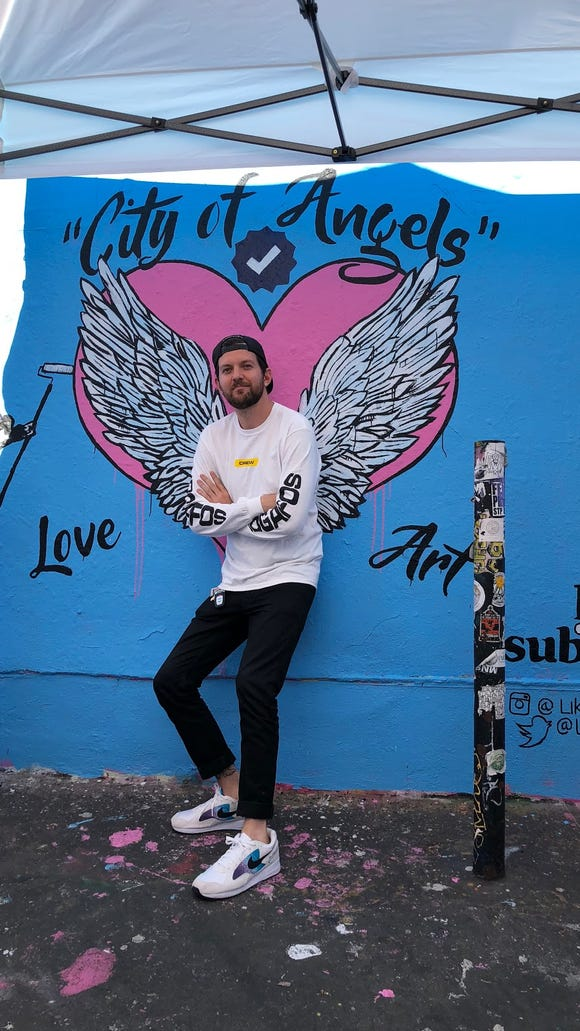 """Dillon Francis, the DJ and star of series """"Like and Subscribe,"""" poses at a VIP mural that promotes his show"""