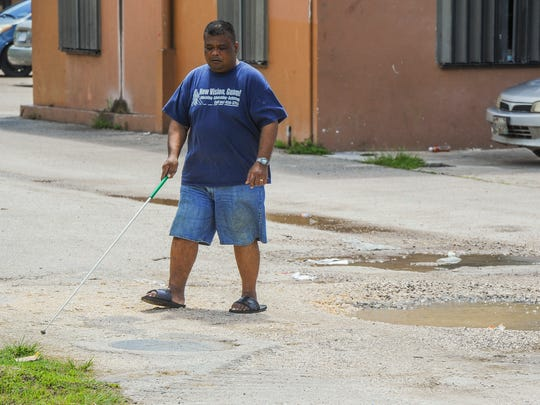 Frank Ungacta, 42, demonstrates how he uses his white cane to avoid obstacles, like mud puddles while walking near the apartment complex on Thursday, Oct. 6, where he resides in Merizo.