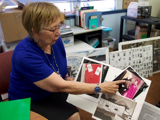 Olivia McDonald reminisces with a photograph of her 1956 graduation on Tuesday, Sept. 12 at Holy Cross Catholic School in Las Cruces. The school is marking its 90th anniversary this week.