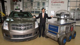 Carnegie Mellon University autonomous driving project chief Raj Rajkumar stands in between the school's first and latest autonomous vehicles, the Terregator, right, and the 2011 Cadillac. CMU has just released a poll on what consumers want in a production version of a self-driving car.