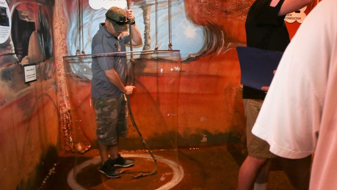 Sgt. 1st Class Ramil Padilla creates a giant bubble in the Custom House Museum Bubble Cave on Friday during a scavenger hunt held by the Adaptive Reconditioning Program at Fort Campbell Warrior Transition Battalion.
