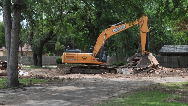 A large demolition machine sits Monday afternoon where a house once stood near Midwestern State University's police department on Hampstead Lane.