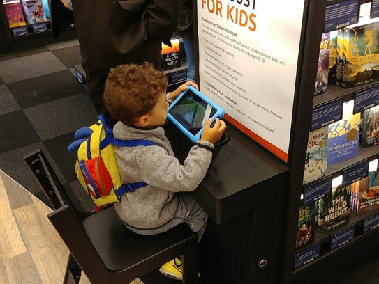 A child plays on a Kindle Fire tablet at the Amazon