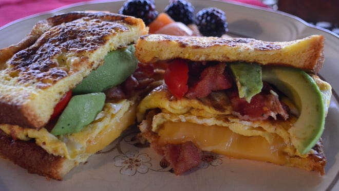 This Savory French Toast Sandwich has it all: French toast, eggs, bacon, mayonnaise, Gouda, avocado, tomato and thinly sliced red onion. Oh yeah, it's delicious.