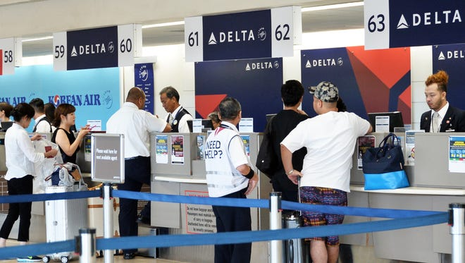 Travelers check-in at the Delta Air Lines counter at the Antonio B. Won Pat International Airport on September 18, 2017. Delta announced that it will stop flying to Guam after Jan. 8, 2018 due to low demand from Japan. It will continue to provide direct flights between Japan and Saipan and Japan and Palau.