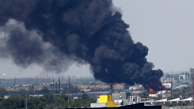 A giant plume of black smoke rises over downtown as a fire burns in a recycling yard Tuesday, July 10, 2018, in northeast Denver. Fire crews from Denver and Adams County responded to the fire, which was reported at EVRAZ Recycling on Tuesday afternoon.  (AP Photo/David Zalubowski)