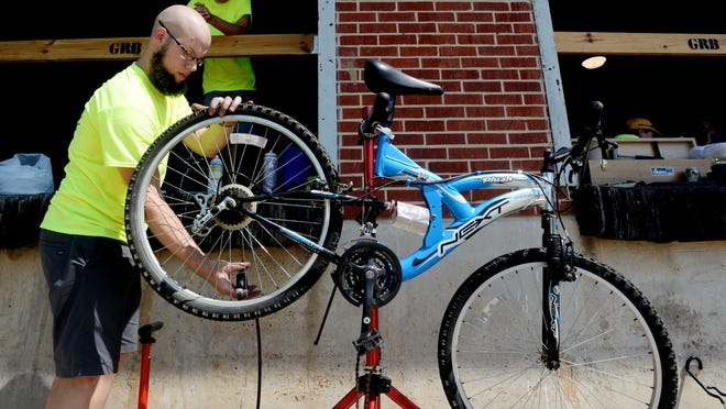 Stephen Pederson, organizer of SBC Bike Social, works on a bicycle during the group's free tune-ups event Saturday afternoon at Great Raft Brewing, 1251 Dalzell St. in Shreveport.