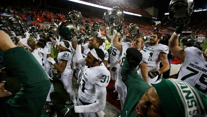 Michigan State players sing their fight song to their fans after their 17-14 win over Ohio State on Saturday.