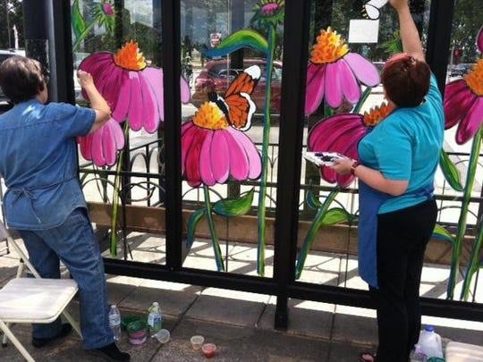 Volunteers paint a bus shelter near the Center 50+.