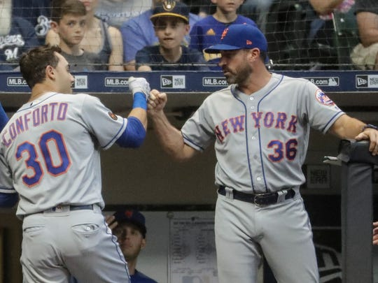 New York Mets manager Mickey Callaway congratulates Michael Conforto after his home run during the fourth inning of a baseball game against the Milwaukee Brewers Friday, May 25, 2018, in Milwaukee.