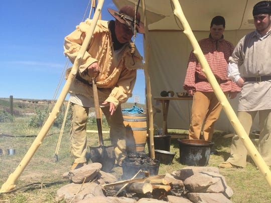 John Toenyes stirs embers at a cooking demonstration at the Lewis & Clark Interpretive Center.
