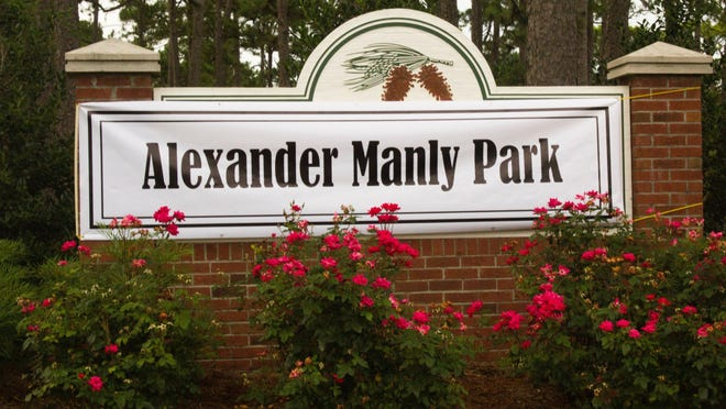 """A sign reading """"Alexander Manly Park"""" was draped over the entrance sign to Hugh MacRae Park in Wilmington on Monday, the latest attempt to push the county to rename the popular park."""