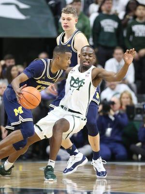 Michigan's Muhammad-Ali Abdur-Rahkman drives against MSU's Joshua Langford in the second half on Saturday in East Lansing.