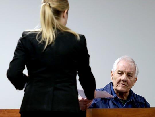 Defendant Larry Mann hands back a copy of a letter