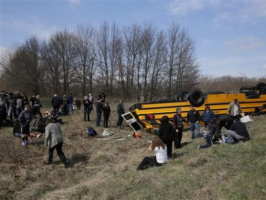 People on the scene of a school bus accident attend