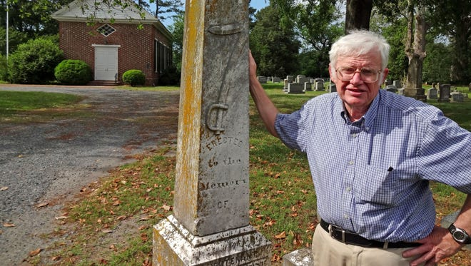 Eastern Shore of Virginia historian Jerry Dought stands next to the memorial of Otho K. West in the graveyard at St. George's Episcopal Church in Pungoteague. West, a Confederate officer, was born on a nearby plantation. The broken sword on the tombstone is a symbol of a fallen officer.