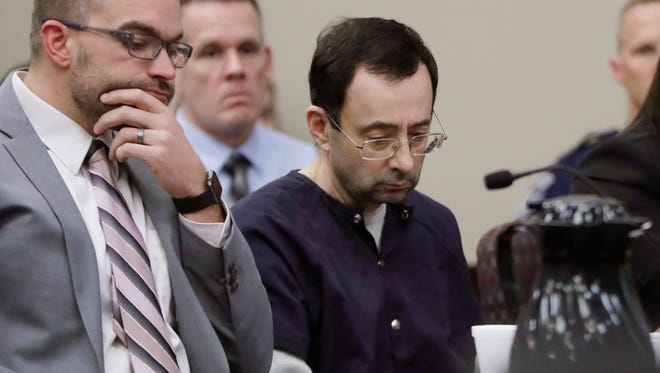 """Larry Nassar sits with attorney Matt Newburg during his sentencing hearing Wednesday, Jan. 24, 2018, in Lansing, Mich. The former sports doctor who admitted molesting some of the nation's top gymnasts for years was sentenced Wednesday to 40 to 175 years in prison as the judge declared: """"I just signed your death warrant.""""  The sentence capped a remarkable seven-day hearing in which scores of Nassar's victims were able to confront him face to face in the Michigan courtroom.  (AP Photo/Carlos Osorio) ORG XMIT: MICO118"""