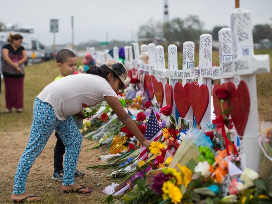 Bella Araiza places flowers Nov. 12, 2017, at a makeshift memorial near First Baptist Church in Sutherland Springs, Texas, where 25 people, including a pregnant woman whose unborn baby also died, were shot to death a week before.