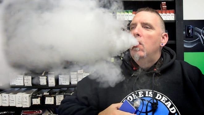LifeSmoke Vapors associate Rick Templin exhales vapor in the shop in Springettsbury Township Wednesday, Oct. 28, 2015. Bill Kalina - bkalina@yorkdispatch.com
