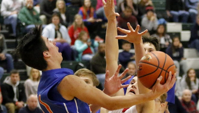 Ryan Benedict of Thomas A. Edison tries for a reverse layup as Troy's Robert Rogers defends Wednesday at the Josh Palmer Fund Elmira Holiday Inn Classic at Elmira High School.