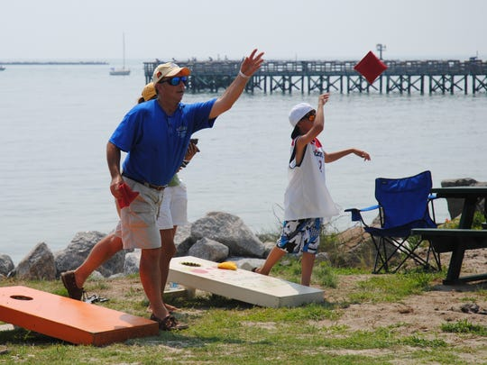 People compete in a bean bag toss game at Cape Charles