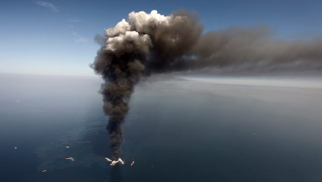 FILE -  In this Wednesday, April 21, 2010 file photo, oil can be seen in the Gulf of Mexico, more than 50 miles southeast of Venice on Louisiana's tip, as a large plume of smoke rises from fires on BP's Deepwater Horizon offshore oil rig. An April 20, 2010 explosion at the offshore platform killed 11 men, and the subsequent leak released an estimated 172 million gallons of petroleum into the gulf. U.S. District Judge Carl Barbier ruled Thursday, Sept. 4, 2014, in New Orleans, La., that BP acted recklessly and bears most of the responsibility for the oil spill. The ruling exposes BP to about $18 million in civil fines under the Clean Water Act. (AP Photo/Gerald Herbert, File)