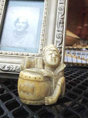 An antique ivory figurine belonging to Ashley Prout McAvey of Shelburne rests beside a photographic portrait of her grandmother, who gave her the carving.