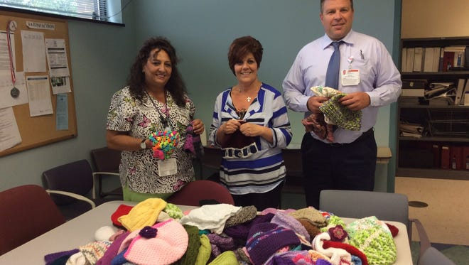 Patti Strittmatter, radiation oncology nurse, Maureen Sarno, cancer registry coordinator and Robert Bozicev, manager of radiation oncology are delighted with the hundreds of hats you made for JFK Medical Center.