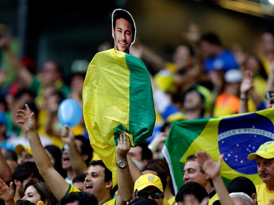 A Brazil supporter holds up a flag draped cutout of Brazil's Neymar before the World Cup semifinal soccer match between Brazil and Germany at the Mineirao Stadium in Belo Horizonte, Brazil, Tuesday, July 8, 2014. (AP Photo/Andre Penner)