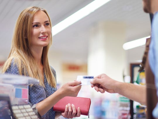 A young woman handing her credit card to a cashier.