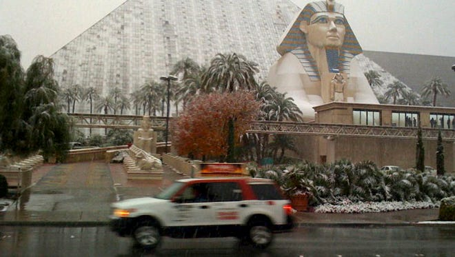 FILE - In this Wednesday, Dec. 17, 2008, file photo, snow covers the sides and sphinx of the Luxor Hotel on the Las Vegas Strip. If Sin City's sports books took bets on the weather, snow in Las Vegas on New Year's Eve would normally have terrible odds. It might pay out for 2014, though, if the white flurries start falling on an Eiffel Tower, a pyramid and a volcano come Wednesday night, Dec. 31, as forecast by the National Weather Service. (AP Photo/Las Vegas Review-Journal, John Gurzinski, File)
