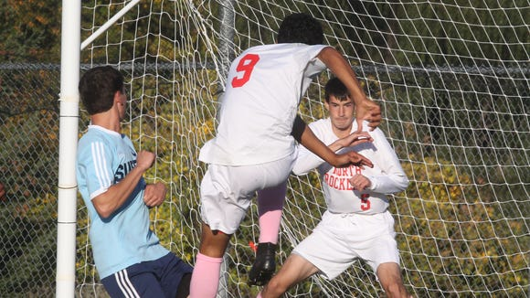 North Rockland's Tyler Piscopiello, center, kicks the ball past his teammate, Lucas Ancin (5), to score the only goal in a 1-0 win over Suffern at North Rockland Oct. 15, 2015.