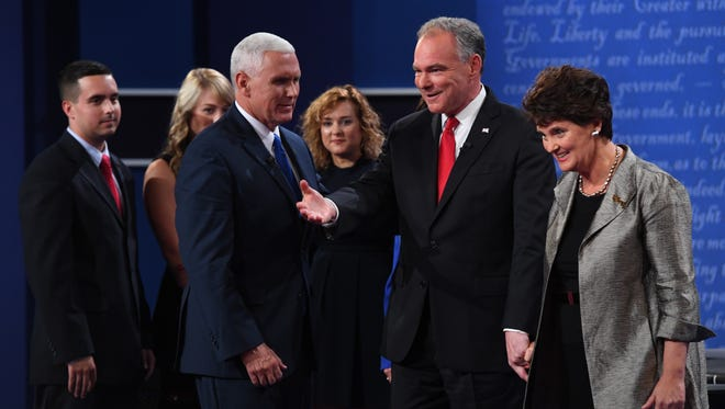 Mike Pence and Tim Kaine talk with family members on stage after the vice presidential debate at Longwood University in Farmville, Va., on Oct. 4, 2016.