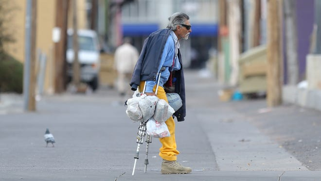 A homeless El Paso man uses crutches to travel downtown. The El Paso Homeless Coalition is looking to get 700 homeless El Pasoans into shelters or otherwise help them in 2018.