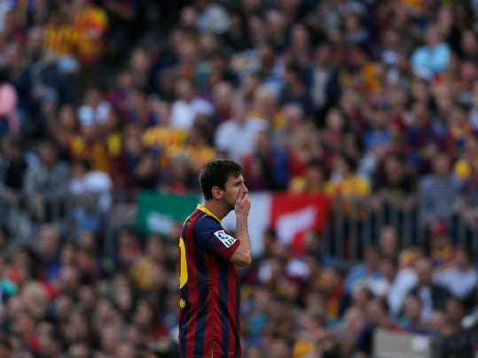 Barcelona's Lionel Messi from Argentina puts his hand on his mouth during a Spanish La Liga soccer match between FC Barcelona and Atletico Madrid at the Camp Nou stadium in Barcelona, Spain, Saturday, May 17, 2014. (AP Photo/Andres Kudacki)