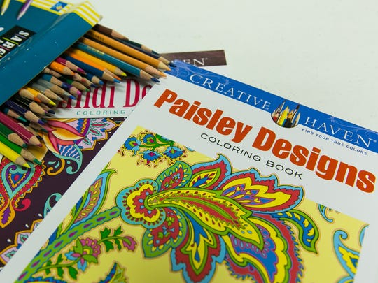Pictured are colored pencils and coloring books used