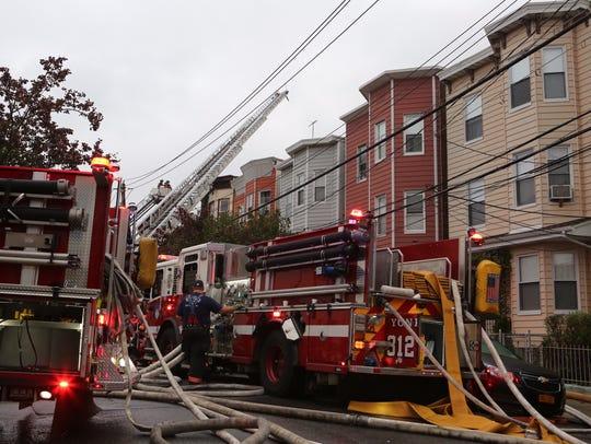 Firefighters battle an apartment building fire on Oak Street in Yonkers on Monday.