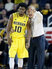 Michigan coach John Beilein gives directions to Derrick Walton Jr. during overtime of a Big Ten game against Wisconsin at Crisler Center on Jan. 24, 2015.
