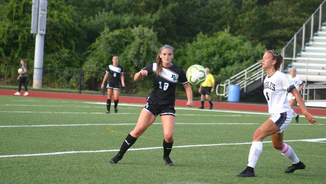 Mary Quinn (left) keeps her eye on the soccer ball in a game last year against Plymouth North. Quinn saw three years of varsity action with the Plymouth South girls soccer and lacrosse programs.