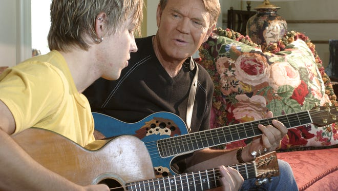 Glen Campbell plays an Ovation brand guitar made by Fender with his son, Cal, in this 2003 file photo.