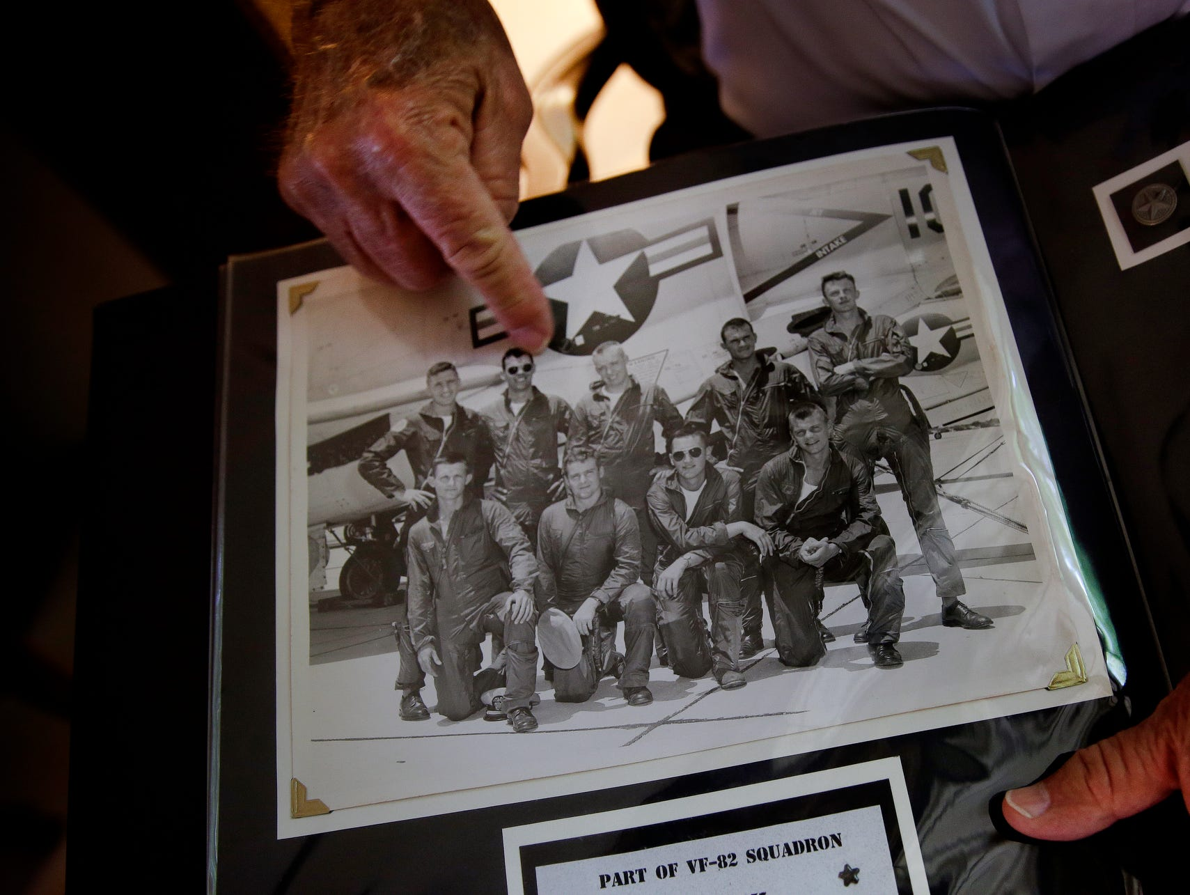 """Jim Graham flips though photos of himself in a Navy photo album inside his Brownsburg home on June 28, 2016. Graham is on the bottom row, second from the left. """"He's died, he died, he died,"""" said Graham as he pointed to half the men in the picture. """"I'm lucky to be alive."""""""