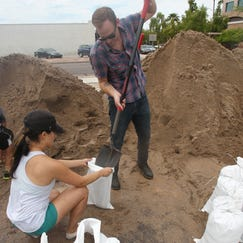 Mercedes Kim (left) and Frank Siino fill up sand bangs for their home in Chandler. Kim found her vehicle nearly under water,Monday morning, on Sept 8, 2014.