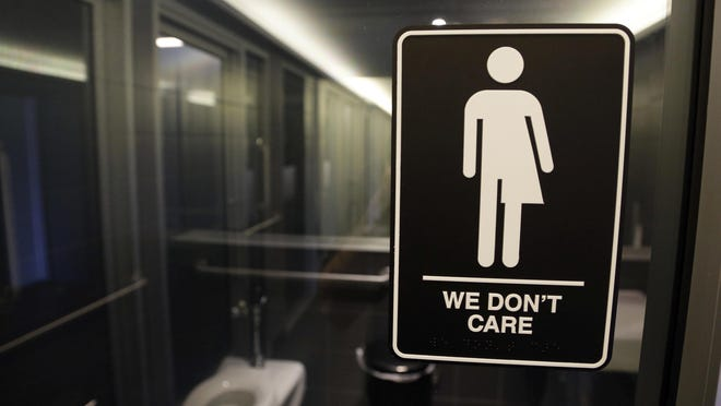 In this May 12, 2016 photo, a gender-free sign hangs outside a restroom at 21c Museum Hotel in Durham.