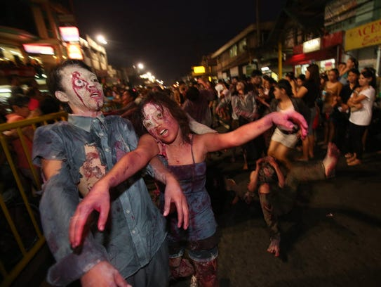 People dressed as zombies join a Halloween Parade in