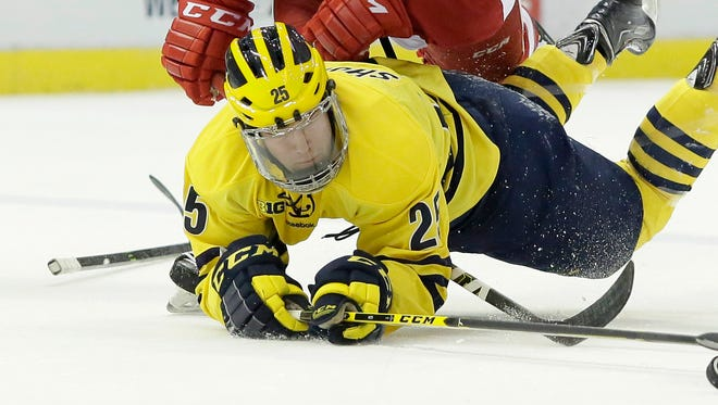 Michigan's Max Shuart (25) is taken to the ice by Wisconsin's Matt Paape (8) during the first period in the Big Ten tournament March 19, 2015, in Detroit.
