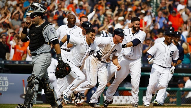 From left, Jose Iglesias, JaCoby Jones and J.D. Martinez lead the charge to swarm Tyler Collins (not pictured) after his sacrifice fly scored Jones with the winning run in the bottom of the ninth inning Wednesday at Comerica Park. The Tigers beat the Chicago White Sox, 3-2.