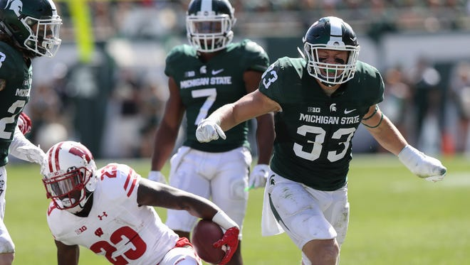 Michigan State linebacker Jon Reschke reacts after tackling Wisconsin's Dare Ogunbowale during the second half Saturday, Sept. 24, 2016, at Spartan Stadium in East Lansing.