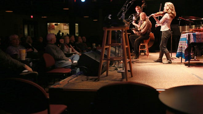Patrons gather around the intimate stage at the Ark to listen to Ann Arbor residents Emily Slomovits, 20, on violin; Laszo Slomovits, 66, on guitar, and Jacob Warren, 19, on bass.